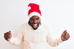 Young african american man wearing Christmas Santa hat over isolated white background very happy and excited doing winner gesture with arms raised, smiling and screaming for success. Celebration