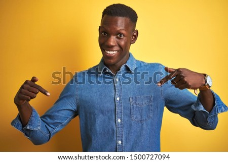 Young african american man wearing denim shirt standing over isolated yellow background looking confident with smile on face, pointing oneself with fingers proud and happy.