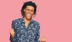 Young african american man wearing 80s shirt very happy and excited doing winner gesture with arms raised, smiling and screaming for success. celebration concept.