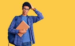 Young african american man wearing student backpack holding book confuse and wondering about question. uncertain with doubt, thinking with hand on head. pensive concept.