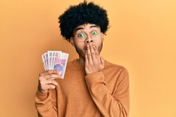 Young african american man with afro hair holding 20 polish zloty banknotes covering mouth with hand, shocked and afraid for mistake. surprised expression