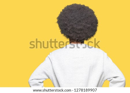 Young african american man with afro hair wearing sporty sweatshirt standing backwards looking away with arms on body