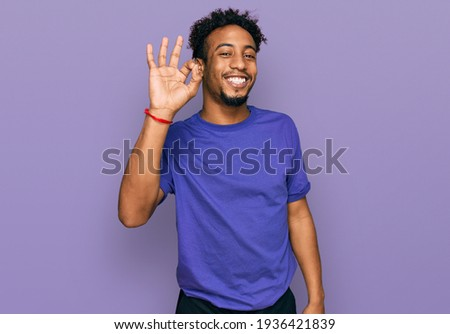 Young african american man with beard wearing casual purple t shirt smiling positive doing ok sign with hand and fingers. successful expression.  Zdjęcia stock ©