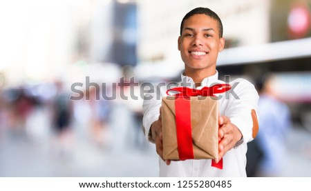 Young african american man with white shirt holding gift boxes in hands in the middle of the city