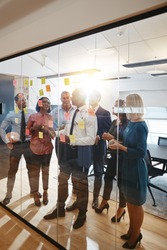 Young African American manager and his smiling team brainstorming together with sticky notes on a glass wall during an office meeting