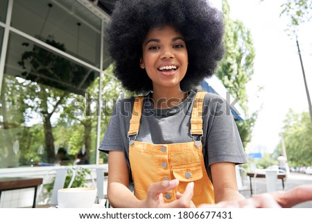 Young African American mixed race hipster vlogger influencer woman with Afro hair looks at webcam talks to camera sits at outdoor cafe table video calling, recording blog, headshot portrait.