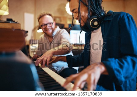 Young African American musican playing keyboards during a recording session with a producer in a studio #1357170839
