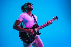 Young african-american musician playing the guitar like a rockstar on blue studio background in neon light. Concept of music, hobby. Joyful attractive guy improvising. Retro colorful portrait.