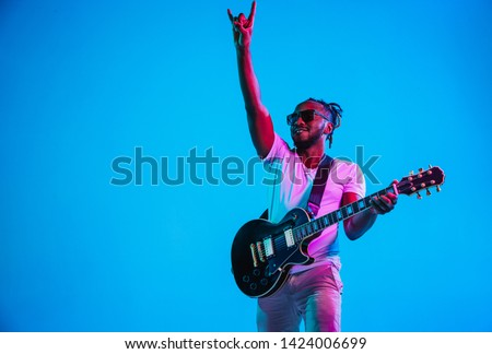 Young african-american musician playing the guitar like a rockstar on blue studio background in neon light. Concept of music, hobby. Joyful attractive guy improvising. Retro colorful portrait. #1424006699