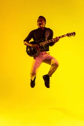 Young african-american musician playing the guitar like a rockstar on yellow background in neon light. Concept of music, hobby, festival, open-air. Joyful attractive guy improvising, singing song.