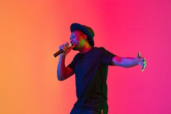 Young african-american musician singing on gradient orange-purple studio background in neon light. Concept of music, hobby, festival. Joyful party host, stand upper. Colorful portrait of artist.