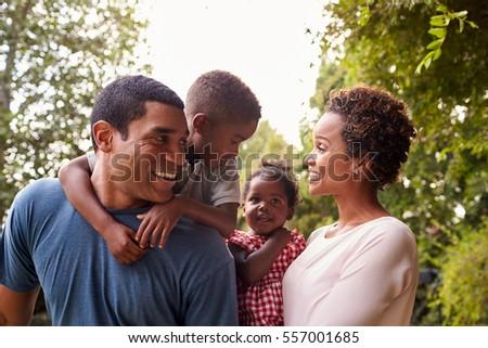 Young African American parents carrying children in garden