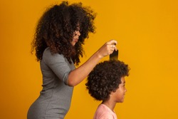 Young african american people combing hair isolated. Fork for combing curled hair. Yellow background.