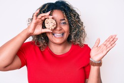 Young african american plus size woman holding cookie celebrating victory with happy smile and winner expression with raised hands