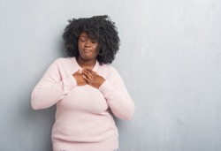 Young african american plus size woman over grey grunge wall wearing winter sweater smiling with hands on chest with closed eyes and grateful gesture on face. Health concept.