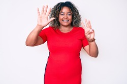 Young african american plus size woman wearing casual clothes showing and pointing up with fingers number eight while smiling confident and happy.