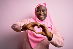 Young african american plus size woman wearing muslim hijab over isolated pink background smiling in love doing heart symbol shape with hands. Romantic concept.