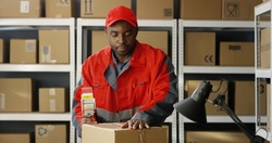 Young African American postal male worker in uniform packing carton box at delievery department in post office. Postman closing parcel with sticky tape. Mail shipping concept.