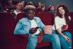 Young African American rewrites in chat using phone. A woman looks at a man who is looking at the phone while sitting in the cinema.