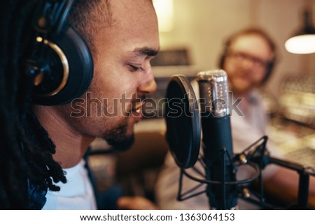 Young African American singer working on a track with a music producer during a session in a recording studio #1363064153
