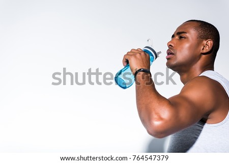 young african american sportsman drinking water from sports bottle on grey #764547379