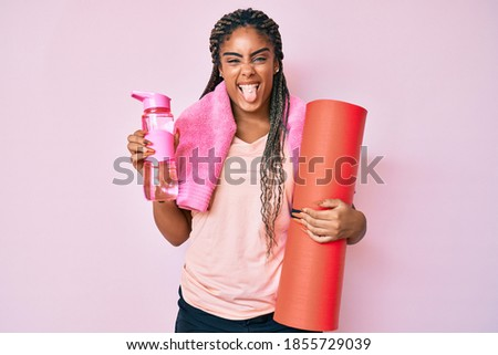 Young african american sporty woman with braids holding yoga mat sticking tongue out happy with funny expression.