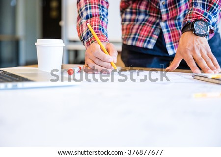 Young african american student drawing blueprint with pencil standing in classroom