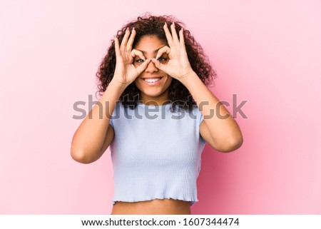 Young african american woman against a pink background showing okay sign over eyes Stock photo ©