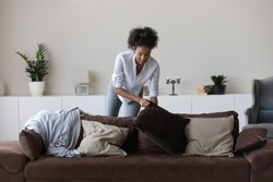 Young African American woman clean cozy new modern apartment or house on weekend day. Millennial biracial female renter or tenant decorate design comfortable couch in living room at home.