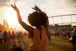 Young African American woman dancing at summer holi festival, back view