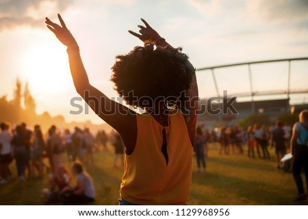 Young African American woman dancing at summer holi festival, back view #1129968956