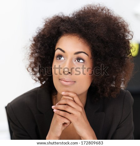 Young African American woman daydreaming sitting staring upwards with a faraway look in her eyes and a gentle smile