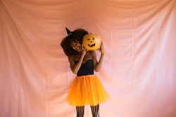young african american woman dressed as a witch for halloween party and holding a pumpkin in her hands. She wears a witch's hat and an orange skirt. The woman smiles at the camera with the pumpkin.