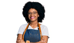 Young african american woman dressmaker designer wearing atelier apron smiling with a happy and cool smile on face. showing teeth.