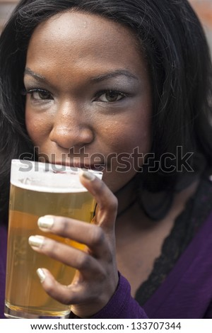 Young African American woman drinks a pale ale from a pint glass.