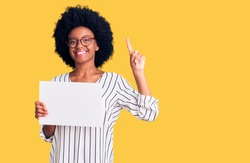 Young african american woman holding blank empty paper surprised with an idea or question pointing finger with happy face, number one