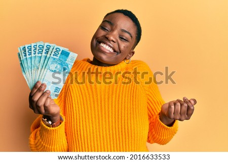 Young african american woman holding 100 brazilian real banknotes screaming proud, celebrating victory and success very excited with raised arm