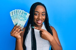 Young african american woman holding 100 brazilian real banknotes smiling happy pointing with hand and finger