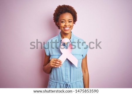 Young african american woman holding brest cancer ribbon over isolated pink background with a happy face standing and smiling with a confident smile showing teeth #1475853590