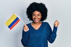 Young african american woman holding colombia flag screaming proud, celebrating victory and success very excited with raised arm