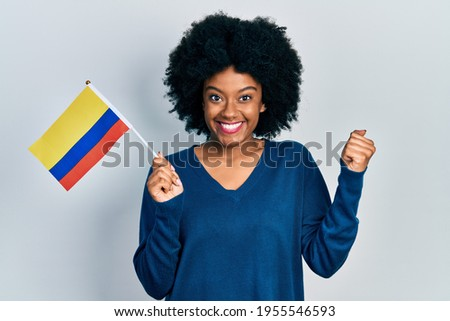Young african american woman holding colombia flag screaming proud, celebrating victory and success very excited with raised arm  Stock fotó ©