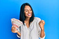 Young african american woman holding 10 colombian pesos banknotes very happy and excited doing winner gesture with arms raised, smiling and screaming for success. celebration concept.