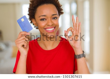 Young african american woman holding credit card doing ok sign with fingers, excellent symbol
