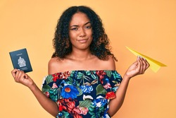 Young african american woman holding paper airplane and canadian passport skeptic and nervous, frowning upset because of problem. negative person.