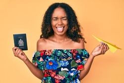 Young african american woman holding paper airplane and canadian passport sticking tongue out happy with funny expression.