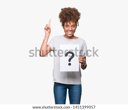 Young african american woman holding paper with question mark over isolated background surprised with an idea or question pointing finger with happy face, number one