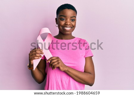 Young african american woman holding pink cancer ribbon thinking attitude and sober expression looking self confident  Сток-фото ©