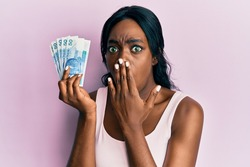 Young african american woman holding 50 polish zloty banknotes covering mouth with hand, shocked and afraid for mistake. surprised expression