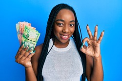 Young african american woman holding south african rand banknotes doing ok sign with fingers, smiling friendly gesturing excellent symbol