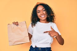 Young african american woman holding take away paper bag smiling happy pointing with hand and finger